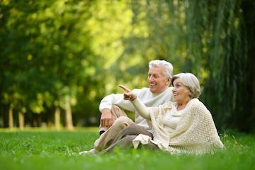 older man and woman happily sitting in park