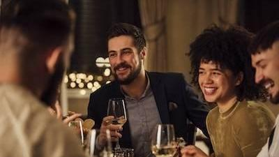 man holding wine glass smiling at dinner party next to smiling woman