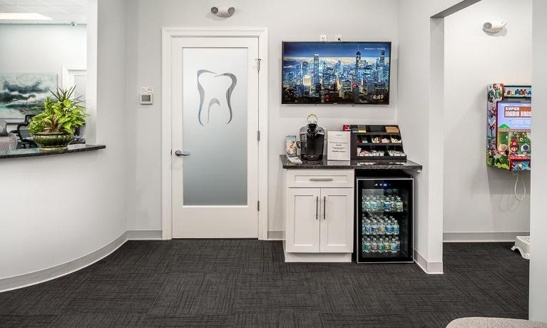 Coffee bar with coffee machine and water bottles in dental waiting room